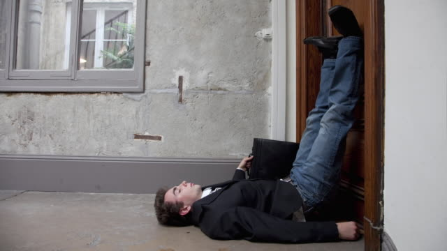 Stop Motion / Pixilation shot of young businessman sleeping on floor in apartment building