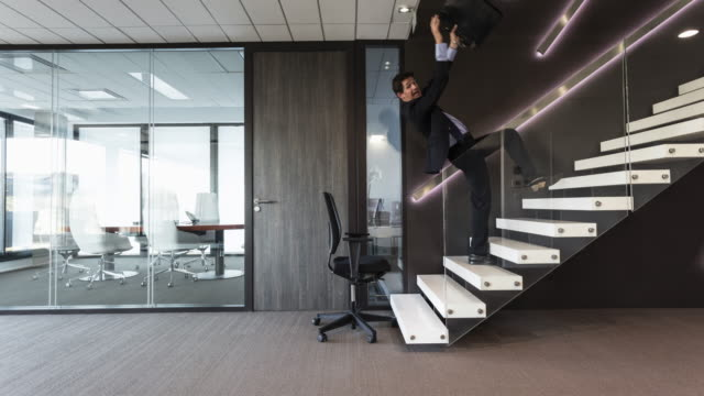 vídeos de stock e filmes b-roll de stop motion shot of businessman falling down backwards in stairs - sorte
