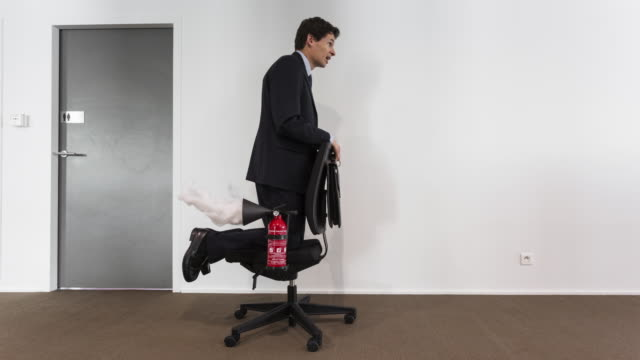 stop motion shot of businessman rolling on seat moved by fire extinguishers used as propellers - lavoro e impiego video stock e b–roll