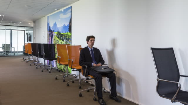 stop motion shot of businessman sitting on office seat rolling like wagon - office chair stock videos & royalty-free footage