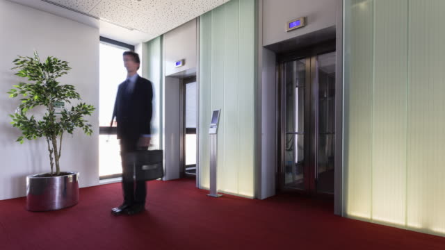 stop motion shot of businessman sliding and turning like a pinwheel in front of lift and finally ejected by plant - オフビート点の映像素材/bロール