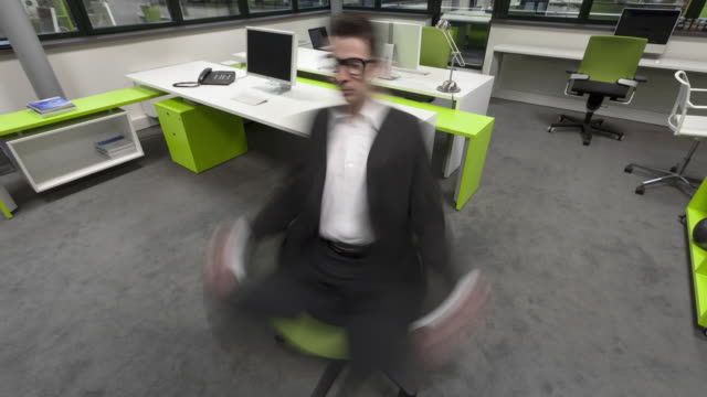 Stop Motion shot of businessman turning on seat while making yoga and expelled from seat by speed
