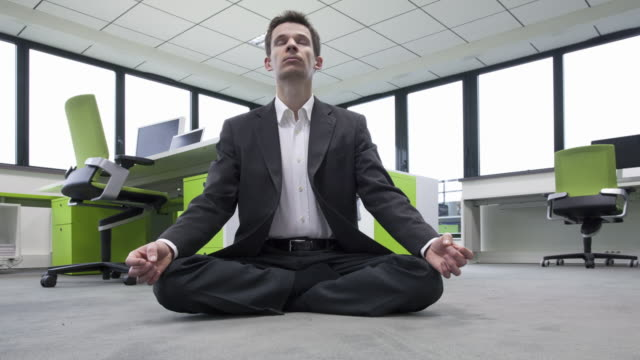 Stop Motion shot of businessman turning on the ground making yoga in his office