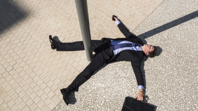 Stop motion shot of knocked down Businessman sliding on floor