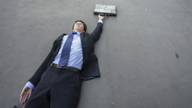 stop motion shot of unconscious businessman sliding on floor pulled by his wallet - overworked stock videos & royalty-free footage