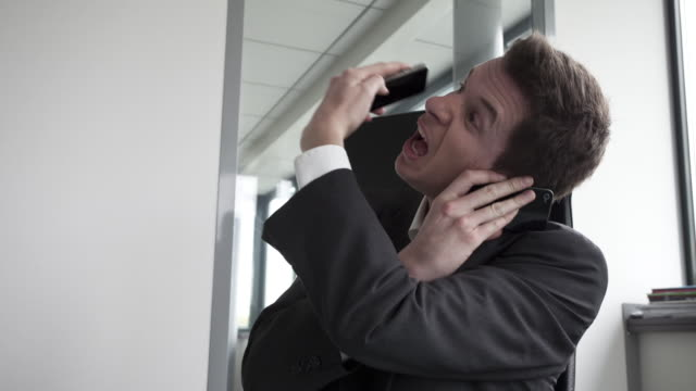 vidéos et rushes de stop motion track shot of businessman agressed by mobile and fix phones - displeased