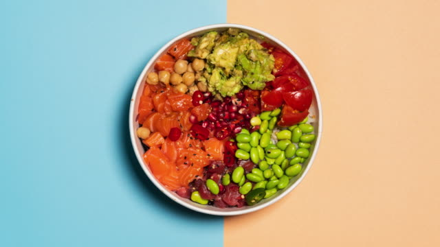 stop motion video of an hawaiian poke bowl with rice, salmon, avocado, tomatoes, tuna, chickpeas, pomegranate and edamame. top view from above. - vegetable stock videos & royalty-free footage