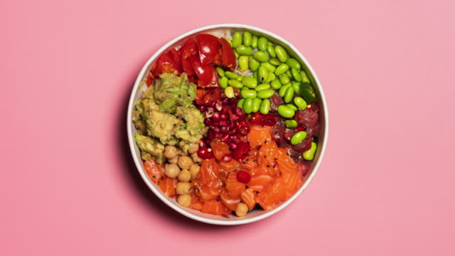 stop motion video of an hawaiian poke bowl with rice, salmon, avocado, tomatoes, tuna, chickpeas, pomegranate and edamame. top view from above. - plate stock videos & royalty-free footage