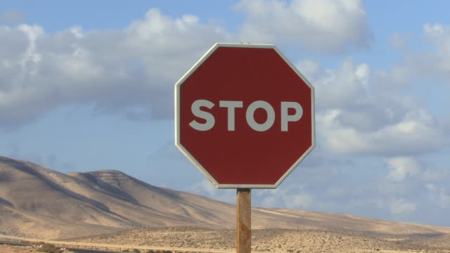 cu, zo, stop sign by rural highway / fuerteventura, canary islands, spain - schild stock-videos und b-roll-filmmaterial