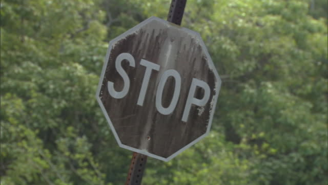 vidéos et rushes de a stop sign shows indications of damage. - exposé aux intempéries