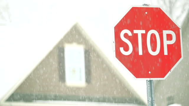 Stop Sign, Snow Storm and Home in Winter