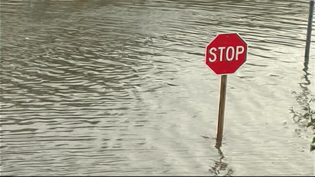 vídeos y material grabado en eventos de stock de stop sign stands in flooded road after hurricane sandy - environment or natural disaster or climate change or earthquake or hurricane or extreme weather or oil spill or volcano or tornado or flooding