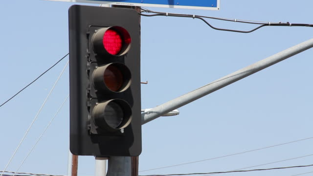 Stoplight turning from red to green during daylight
