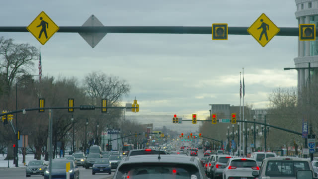 stopping at a red light in traffic in downtown park city, utah on an overcast day - park city utah stock videos & royalty-free footage