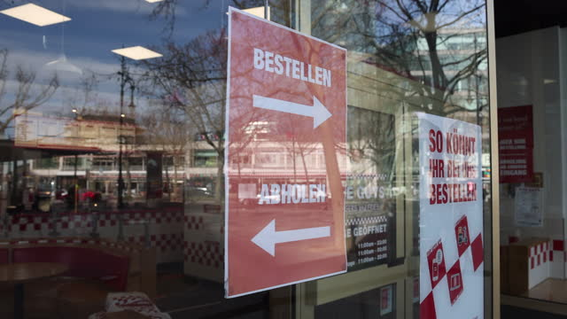 store advertises shopping service on a poster displayed in the shop window on kurfuerstendamm shopping avenue on the first day since december stores... - opening stock videos & royalty-free footage