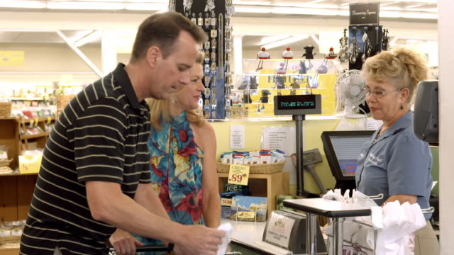 MS store checker hands plastic shopping bag full of groceries to middle aged couple while young woman waits for her groceries being scanned and bagged by another cashier / Cabazon, California, USA