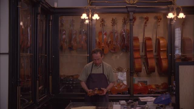 a store clerk examines a violin. - 陳列ケース点の映像素材/bロール