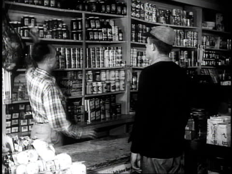 1950 MONTAGE store clerk helping a customer at a country store / Southville, Kentucky, United States