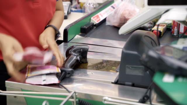 スーパーマーケットストアでバーコード製品をスキャンする店員。 - レジ係点の映像素材/bロール