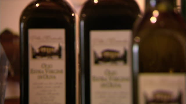 a store displays bottles of extra-virgin olive oil. - olive oil stock videos & royalty-free footage