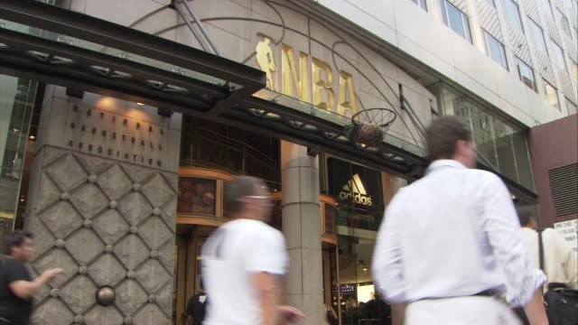 ms nba store entrance, 666 5th avenue, pedestrians walking by in foreground / manhattan, new york city, new york, usa - fifth avenue stock-videos und b-roll-filmmaterial