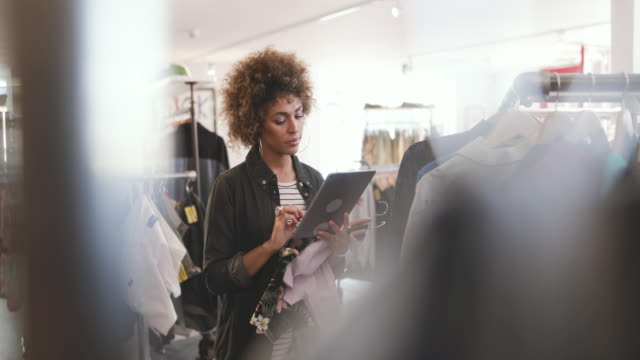 stockvideo's en b-roll-footage met store manager using digital tablet in a clothing store - klein