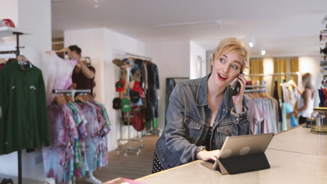 store manager using digital tablet in a clothing store - armeria negozio video stock e b–roll