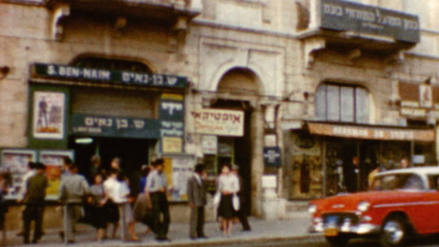 Store on Jaffa Street with soldiers waiting for bus / Donkey pulling cart / Egged Buses / City Hall / Jaffa Street on May 01 1962 in Jerusalem Israel