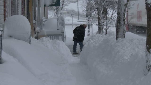 a store owner digs out the walkway in front of his store on main street in adams new york after a blizzard dropping several feet of snow hits the area - scott mcpartland stock videos & royalty-free footage