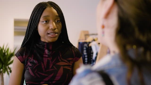 vídeos de stock, filmes e b-roll de a store owner helps a young female customer try on accessories at an african-themed clothing boutique - jaqueta jeans