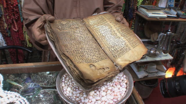 cu zi td store owner holding parchment book with old semitic writing, muscat, oman - parchment stock videos & royalty-free footage