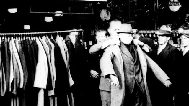 Store owner Louis Cumonow gives away 500 coats to unemployed men during the Great Depression / store workers put coats on unemployed men who have...