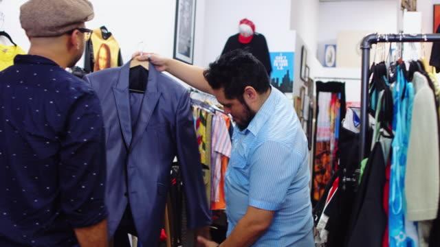 Ladenbesitzer zeigt Kleidung zu Kunden