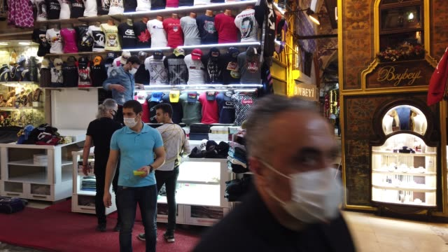 store owners clean their shops and stock in istanbul's famous grand bazaar after it reopened after being shut down for weeks due to the spread of the... - istanbul stock-videos und b-roll-filmmaterial