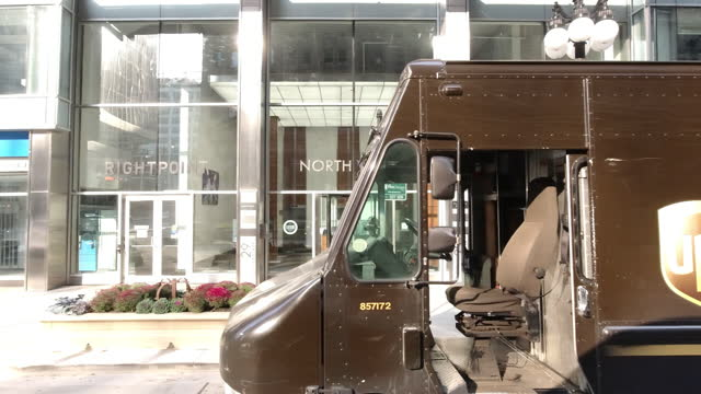 chicago illinois usa octomber 10 2020 ups store with open sign and its trucker on the empty street in the weekend amid the 2020 global covid19... - store sign stock videos & royalty-free footage