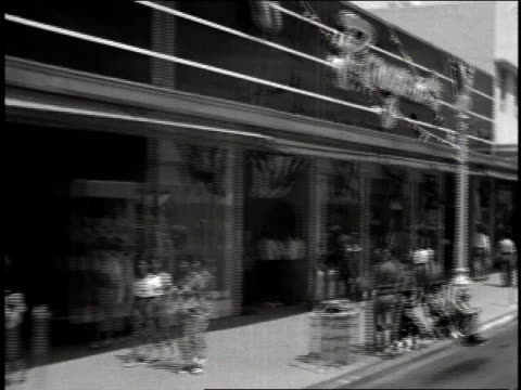 ws storefronts along a street - 1935 stock-videos und b-roll-filmmaterial