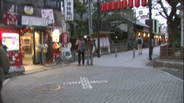 storefronts and a sign lead to the entrance of the shibamata taishakuten temple in tokyo. - shibamata stock videos & royalty-free footage