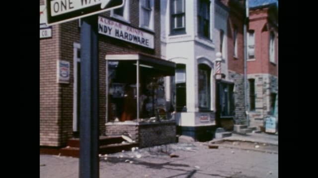 storefronts show damage after riots with a cu a sign reading soul brothers - ワシントンdc点の映像素材/bロール