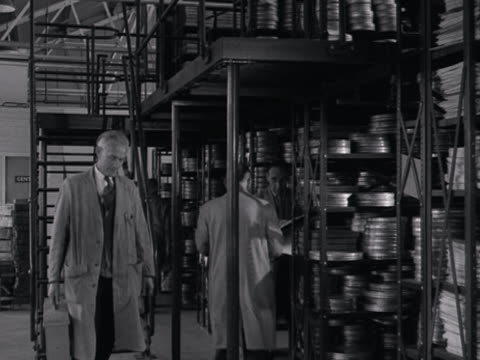 vidéos et rushes de storemen work in the film vaults at the rank offices in london. - boîte de film