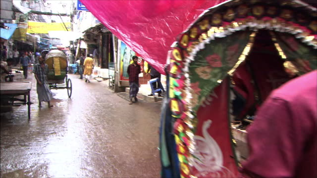 Stores along the street Rickshaws and people pass each other Dolly Shot Shot from the rickshaw