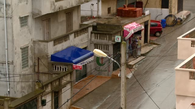 Stores and apartment buildings line a street in a neighbourhood of Algiers. Available in HD.