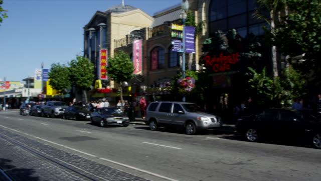 stockvideo's en b-roll-footage met stores line a street near pier 39. - pier 39