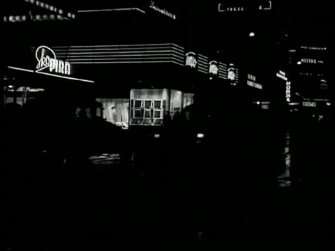 stores w/ lights on, people walking sidewalk, cars passing fg. woman walking dog window shopping. royal' movie theater w/ 'anna lans' marquee. neon... - stockholm stock-videos und b-roll-filmmaterial