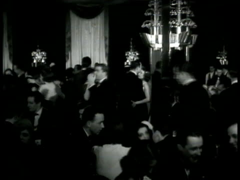 vídeos y material grabado en eventos de stock de ext 'stork club' int men in tuxedos dancing w/ women in gowns some sitting at dinner table fg woman w/ fur coat seated at table woman singing on... - 1940