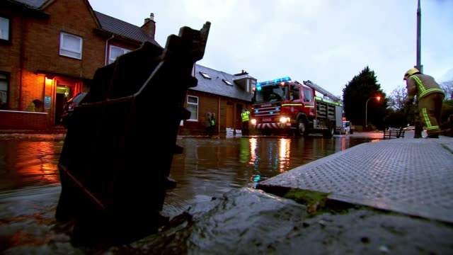 Storm Abigail hits north of country SCOTLAND EXT Firefighter clearing drain in flooded street Firefighters and fire engine in flooded street/ Alison...
