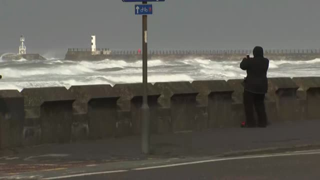 Two people killed SCOTLAND North Ayrshire EXT Back view of person on seafront taking photograph of crashing waves on beach