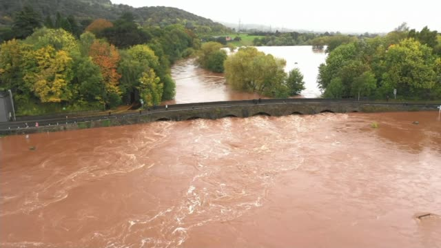 man killed by landslip in wales wales carmarthenshire footage heavily flooded river under bridge james davies interview sot flood by building site - weather stock videos & royalty-free footage