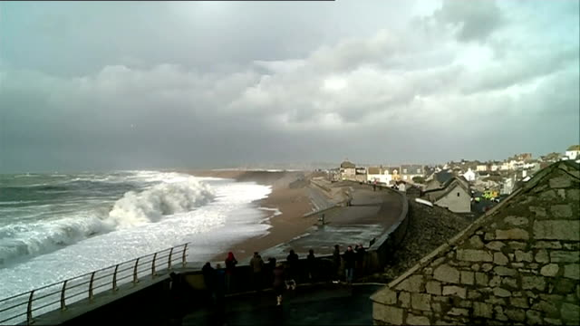 chesil beach in dorset; england: dorset: chesil beach: ext people standing at seafront wall and being drenched by sea water / man and woman being... - drenched stock videos & royalty-free footage