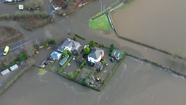 air views of flooding along the england/wales border; england: cheshire: northwich: ext air views flooded fields, houses, gardens, cars in northwich,... - walking in water stock videos & royalty-free footage