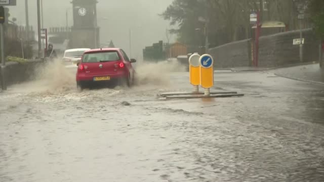 gvs sowerby flooding england west yorkshire sowerby traffic along flooded road / emergency services / flooded houses / more town centre flooding - rain stock videos & royalty-free footage